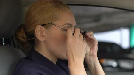 squad car : Female patrol officer putting on sunglasses in squad auto, ready for action