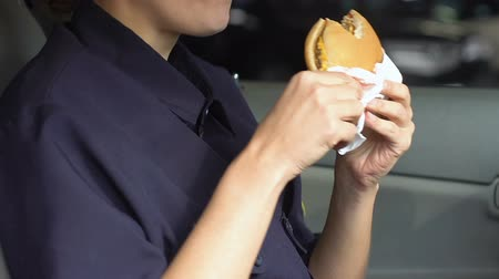 squad car : Patrol woman chewing fatty burger in car, hungry police officer, unhealthy food Stock Footage