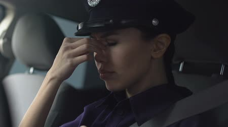 squad car : Asian lady police officer rubbing nasal bridge and taking off hat after hard day