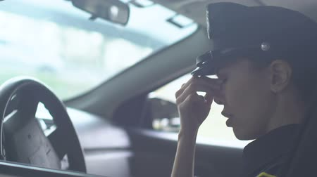 squad car : Tired policewoman taking off cap in squad auto, exhausting work, hard duty