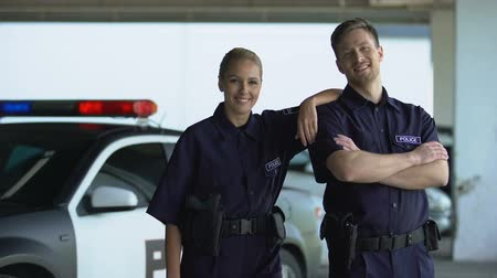 law enforcement : Two patrol officers smiling to camera standing on parking lot, ready for duties Stock Footage