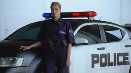 мониторинг : Confident policewoman in uniform leaning on patrol car, maintenance of order