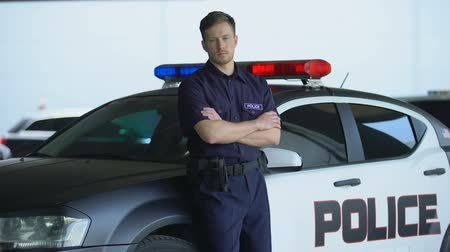 patrolman : Professional policeman in uniform with crossed hands leaning on patrol car, duty Stock Footage