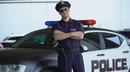 erő : Handsome police officer smiling, standing near new patrol car, law and order