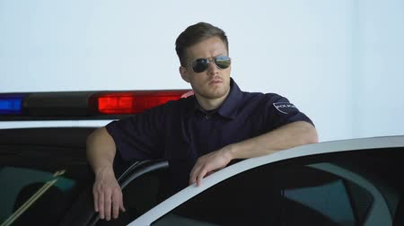 patrolman : Serious patrolman in sunglasses monitoring road standing near door of police car