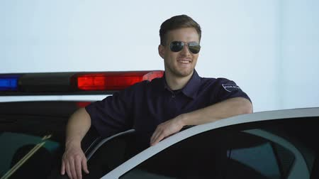 patrolman : Friendly policeman in sunglasses standing near car and smiling, law and order Stock Footage