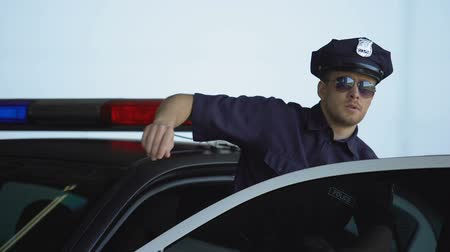 patrolman : Brave policeman in uniform and sunglasses getting out from patrol car, duties Stock Footage