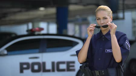 squad car : Serious policewoman putting on sunglasses and posing to camera, public safety Stock Footage