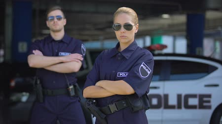 охранять : Serious woman and man police officers in sunglasses standing outdoor, safety