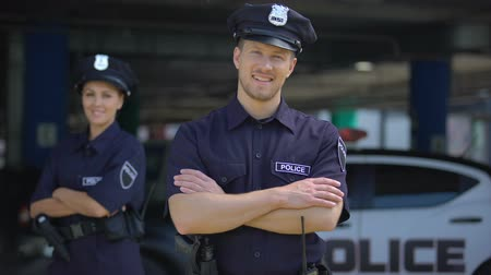 law enforcement : Kind police officers smiling standing near police station, ready to help, order Stock Footage