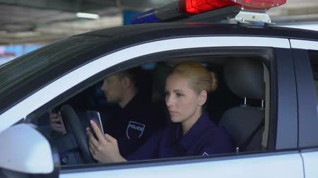 patrolman : Patrol officers chatting and reading news on smartphones sitting in car, break