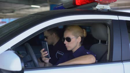 politievrouw : Female and male officers monitoring road situation through online application Stockvideo