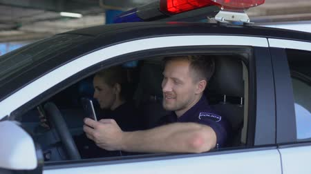 опытный : Professional cop blogging about police officers life, using phone sitting in car