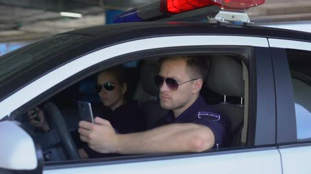 patrolman : Serious police officers monitoring road accidents using mobile app on phone