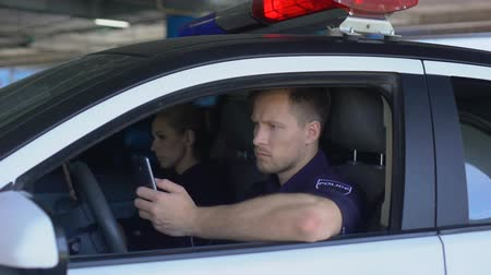 patrolman : Man and woman cop using smartphones sitting in patrol car, monitoring city app