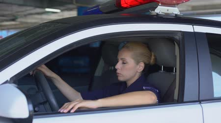 squad car : Exhausted female cop officer in police car after hard work day, stressful job
