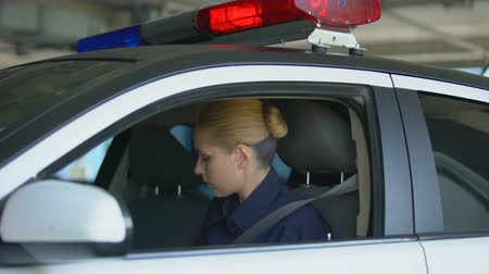 squad car : Police woman wearing safety belt and sunglasses, looking at camera, patrolling Stock Footage
