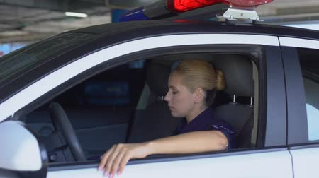 law enforcement : Tired police woman taking off hat, sitting in squad car, exhausted sub work Stock Footage