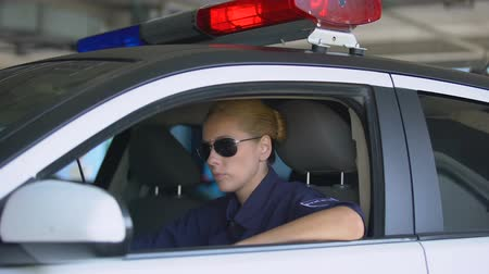 squad car : Serious police woman with walkie-talkie in squad car taking call, emergency Stock Footage