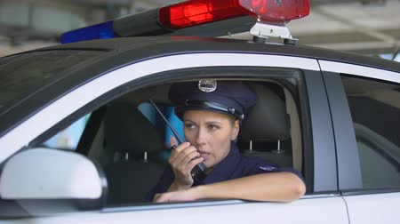 squad car : Police woman in car taking on portable radio, informing during area patrolling