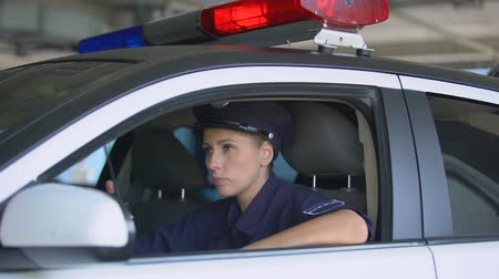 squad car : Female cop talking on walkie-talkie, responding emergency call, crime prevention Stock Footage
