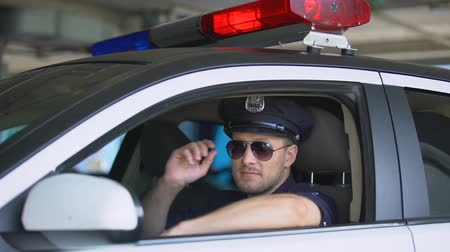 squad car : Young policeman wearing sunglasses in car and smiling at camera, important job