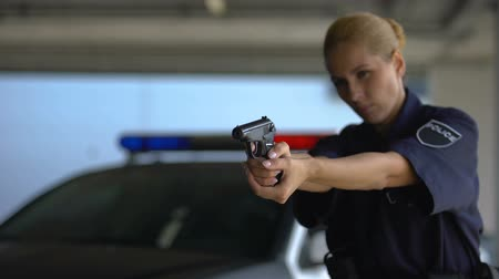 politievrouw : Female police officer aiming gun into criminal, dangerous work, crime prevention