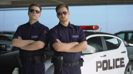 squad car : Confident male officers in sunglasses standing against police car background