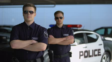 squad car : Male officers in sunglasses standing with hands crossed against police car Stock Footage