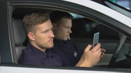squad car : Male police officers chatting smartphones in car during work brake, rest Stock Footage