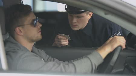 регулировать : Serious policeman checking male drivers license after exceeding speed limit
