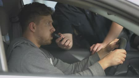 take blood : Drunk male driver passing alcohol test blowing in breath analyzer police control