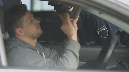 engedély : Policeman checking nervous male drivers documents, searching for wanted criminal