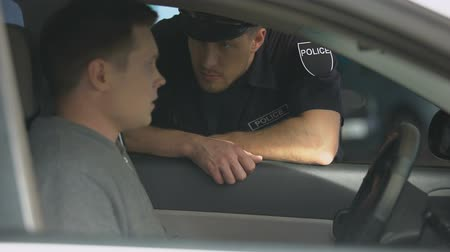 code de la route : Policeman knocking car window, checking license of nervous male driver, control Vidéos Libres De Droits