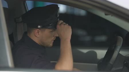 squad car : Tired male officer getting into car after hard workday, stressful job, problems