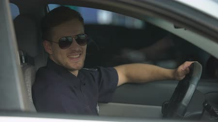 squad car : Cheerful male cop wearing sunglasses sitting in patrol car and smiling at camera