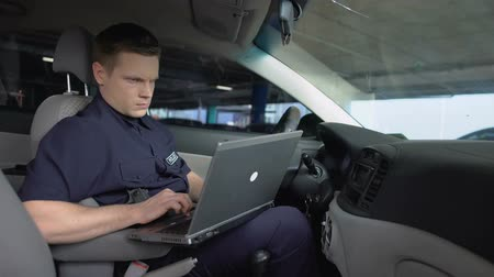 patrol : Policeman working on laptop in patrol car, monitoring incident map, technology