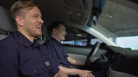 squad car : Cheerful police mates laughing in patrol car during daily duty, friendship