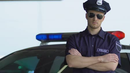 fidedigno : Professional policeman in sunglasses standing near car, district security