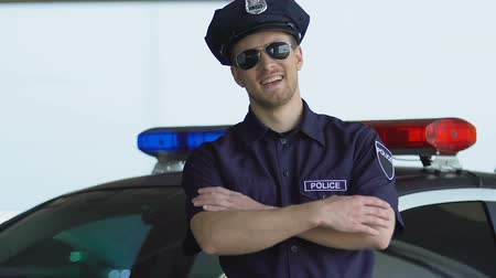 fidedigno : Handsome police officer smiling, standing near cop car, patrolling district