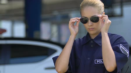 behulpzaam : Police woman in uniform wearing sunglasses, dress code, professional ethics Stockvideo