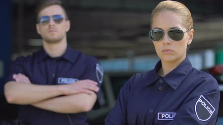 fidedigno : Respectable police officers in sunglasses looking into camera, patrolling city