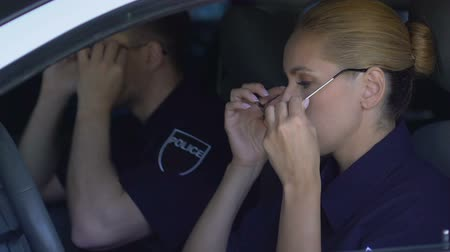 politievrouw : Police teammates wearing sunglasses sitting in car, patrol ready to rescue Stockvideo