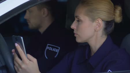 телефон доверия : Police officers monitoring emergency calls in cellphone while sitting in car