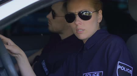 acil : Sad police woman and male partner getting in car, depressed about lost criminal Stok Video