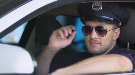 охранять : Friendly policeman putting on sunglasses and smiling sitting in patrol car Стоковые видеозаписи