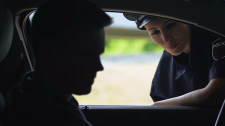 engedély : Friendly patrolwoman knocking on car window and checking driver license, on duty