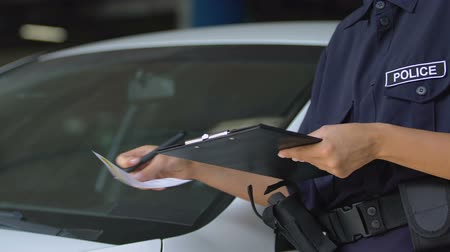 multa : Female parking warden signing ticket and attaching it to car windshield, rules Vídeos