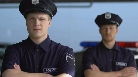 guards : Self-confident cops crossing hands on chest looking into camera, professionals Stock Footage