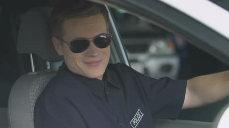 охранять : Responsible policeman in sunglasses sitting in patrol car, smiling to camera Стоковые видеозаписи